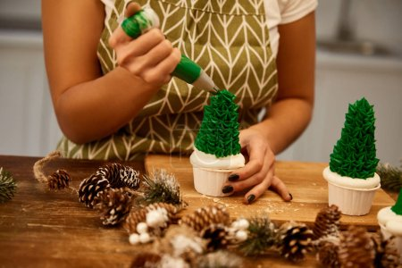 Photo pour Cropped view of confectioner adding green sweet cream on Christmas tree cupcakes with spruce cones on table - image libre de droit