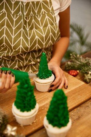 Photo pour Vue recadrée du confiseur décorant les cupcakes d'arbre de Noël à côté des branches d'épinette et des boules de Noël sur la table - image libre de droit