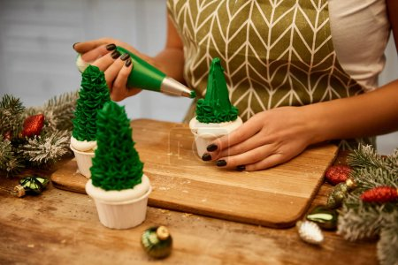 Photo for Cropped view of confectioner making Christmas tree cupcakes beside spruce branches and christmas balls on table - Royalty Free Image