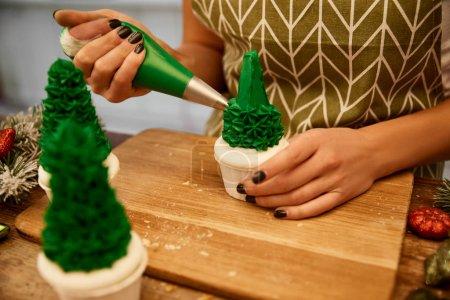 Photo pour Vue agrandie d'un confiseur ajoutant de la crème sucrée aux petits gâteaux aux arbres de Noël avec des branches de pin et des boules de Noël sur la table - image libre de droit