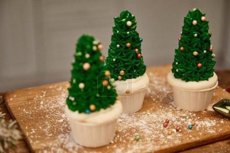 Photo pour Concentration sélective des cupcakes de sapin de Noël avec farine et boule de Noël sur planche à découper - image libre de droit