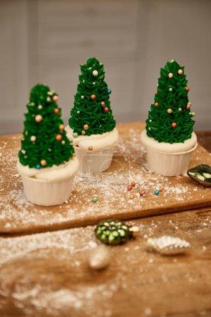 Photo pour Gâteaux de sapin de Noël savoureux avec crème verte et décorations sur planche à découper avec boules de Noël - image libre de droit