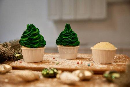 Photo pour Concentration sélective de délicieux cupcakes avec boules de Noël et branche d'épinette sur la table - image libre de droit