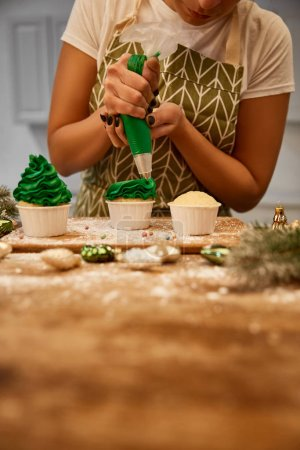 Photo for Cropped view of confectioner working with green cream and cupcakes beside baubles and pine branches on table - Royalty Free Image