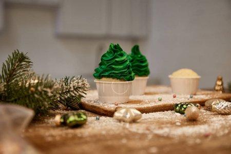 Photo pour Gâteaux savoureux avec crème verte sur la table avec boules de Noël et branche de pin sur la table - image libre de droit