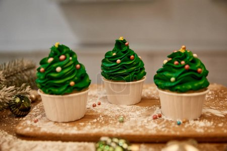 Photo for Decorated cupcakes with green cream and christmas balls with spruce branch on table - Royalty Free Image