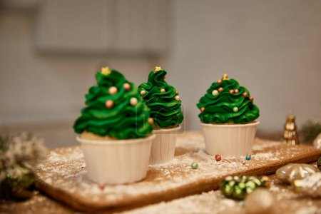 Photo for Selective focus of sweet cupcakes with christmas balls and spruce branch on cutting board - Royalty Free Image