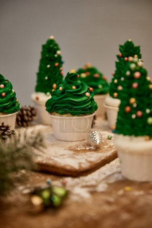 Photo pour Selective focus of decorated Christmas tree cupcakes with sweet cream and spruce cones on table - image libre de droit