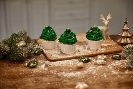 Photo for Cupcakes with sugar sprinkles and christmas balls with spruce branches on table - Royalty Free Image