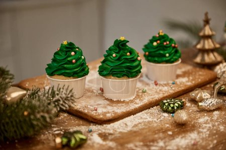 Photo pour Tasty cupcakes with christmas balls and spruce branch on table - image libre de droit