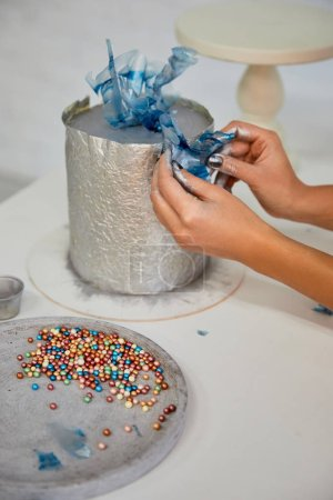 Photo for Cropped view of confectioner decorating cake with sugar sprinkles on table - Royalty Free Image