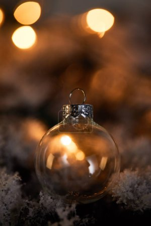 Photo pour Transparent christmas ball on spruce branches in snow with blurred yellow lights in dark - image libre de droit