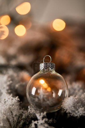 Photo for Transparent christmas ball on spruce branches in snow with blurred yellow lights - Royalty Free Image