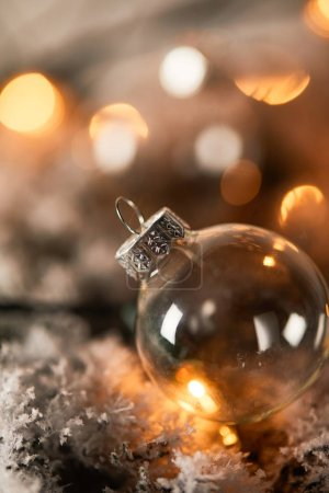 one transparent christmas ball on spruce branches in snow with blurred yellow lights
