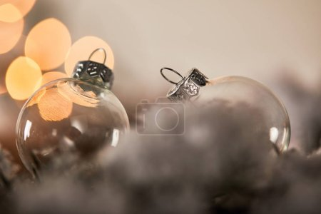 Photo for Transparent christmas balls on spruce branches in snow with yellow lights bokeh - Royalty Free Image