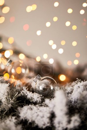 Photo for Transparent christmas balls on spruce branches in snow with blurred yellow lights - Royalty Free Image