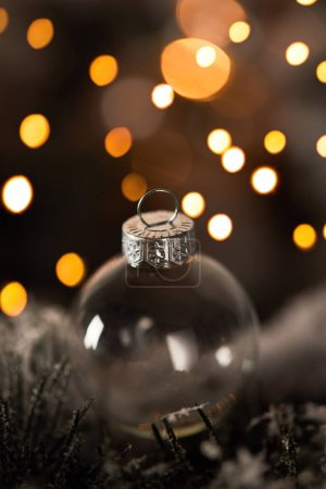 Photo pour Close up of transparent christmas ball on spruce branches in snow with yellow lights bokeh - image libre de droit