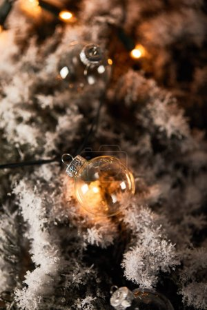 Photo pour Selective focus of transparent christmas balls and yellow lights on spruce branches in snow - image libre de droit