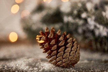 Photo pour Close up of pine cone on wooden table with spruce branches in snow and christmas lights bokeh - image libre de droit