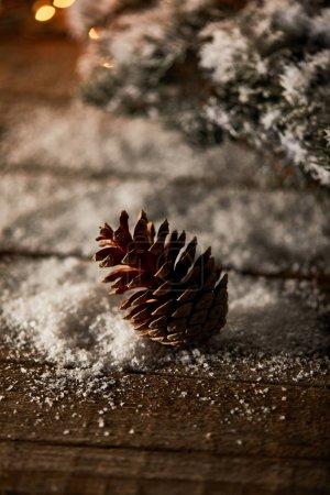 Photo pour Cône de pin sur table en bois avec branches d'épinette et neige à Noël - image libre de droit