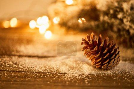 Foto de Decorative pine cone on wooden table with spruce branches in snow and christmas lights bokeh - Imagen libre de derechos