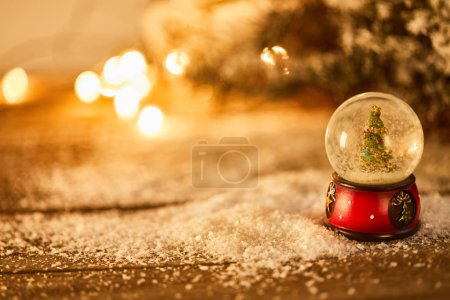 Photo for Little snowball with christmas tree standing on wooden table in snow with spruce branches and blurred lights at night - Royalty Free Image