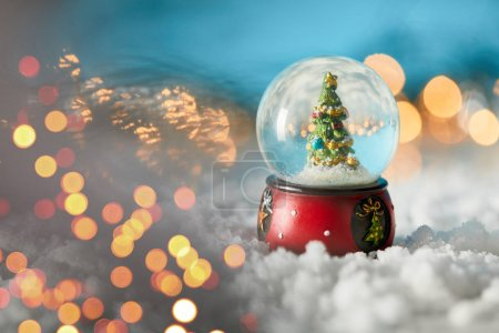 Photo for Christmas tree in snowball standing on blue with snow and blurred lights - Royalty Free Image