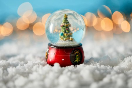 Photo pour Snowball with christmas tree standing on blue with snow and blurred lights - image libre de droit