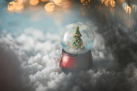 Foto de Selective focus of decorative snowball with christmas tree standing on blue in snow with lights bokeh - Imagen libre de derechos