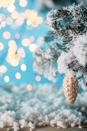 Photo for Spruce branches in snow with christmas ball pine cone and blurred lights on blue - Royalty Free Image