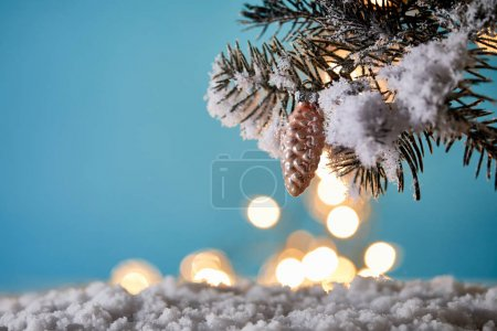 Photo pour Christmas tree in snow with decorative pine cone and christmas lights bokeh on blue - image libre de droit