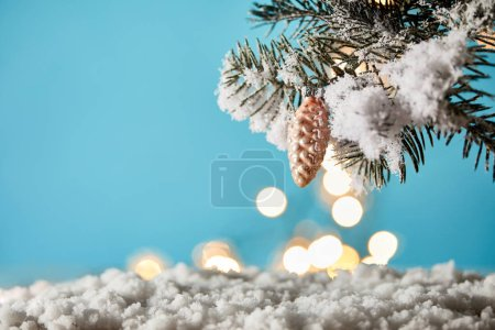 Photo for Christmas tree branches in snow with decorative pine cone and christmas lights bokeh on blue - Royalty Free Image