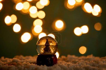 Photo pour Petite boule de neige avec arbre de Noël debout dans la neige avec lumières brouillées la nuit - image libre de droit