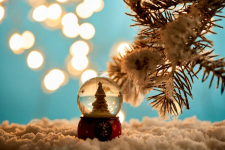 Photo for Decorative christmas tree in snowball standing on blue with spruce branches in snow and blurred lights - Royalty Free Image