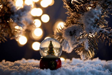 Photo for Decorative christmas tree in snowball standing in snow with spruce branches and blurred lights at night - Royalty Free Image