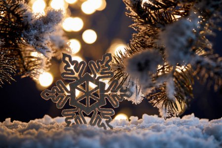 Photo for Close up of decorative snowflake with spruce branches in snow with blurred christmas lights - Royalty Free Image