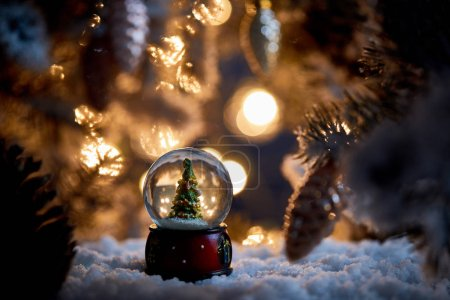 Photo for Little christmas tree in snowball standing in snow with spruce branches and blurred lights at night - Royalty Free Image