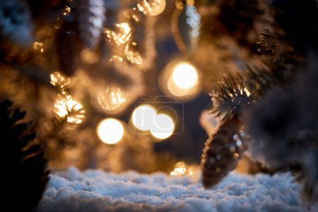 Photo for Close up of christmas tree with decorative christmas balls on snow with blurred lights in dark - Royalty Free Image