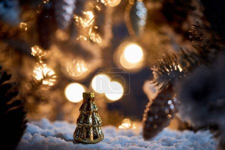 Photo pour Close up of christmas tree with decorative christmas balls on snow with lights bokeh at night - image libre de droit