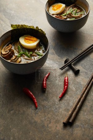 Photo for Traditional spicy ramen in bowls near chopsticks and vegetables on stone surface - Royalty Free Image