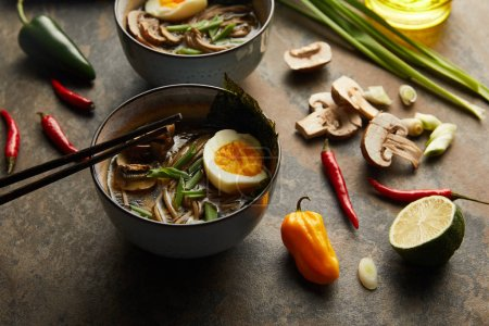 Photo for Traditional spicy ramen in bowls with chopsticks and vegetables on stone surface - Royalty Free Image