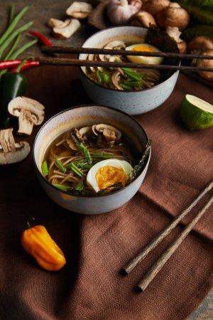 ramen picante tradicional en cuencos con palillos y verduras en la servilleta marrón en la superficie de piedra