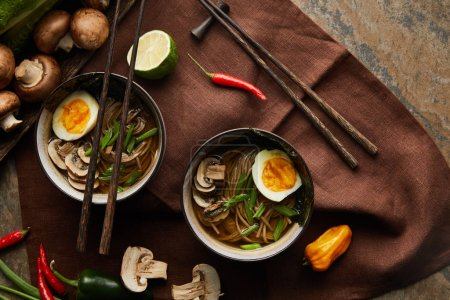 Photo for Top view of traditional spicy ramen in bowls with chopsticks and vegetables on brown napkin on stone surface - Royalty Free Image