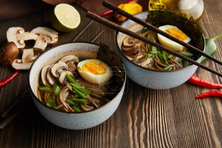 Photo for Traditional spicy ramen in bowls with chopsticks and vegetables on wooden table with napkin - Royalty Free Image