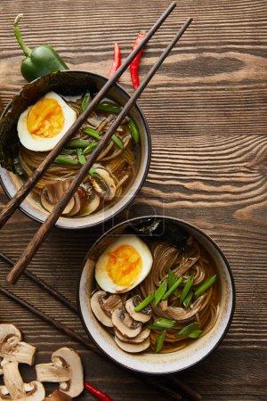 Photo pour Top vue de ramen traditionnel épicé en bols avec baguettes et légumes sur table en bois - image libre de droit