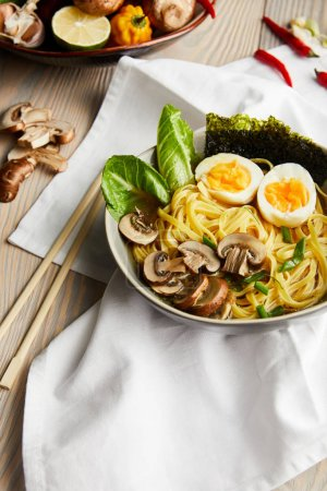 Photo for Traditional asian ramen in bowl near chopsticks, napkin and vegetables on wooden table - Royalty Free Image