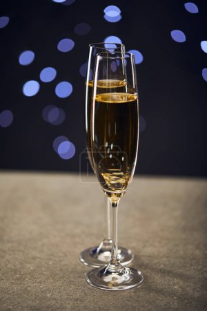 Photo for Sparkling wine in two glasses with blue christmas lights bokeh - Royalty Free Image