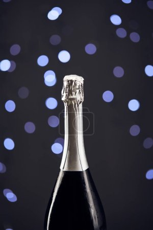 Photo for Close up of sparkling wine bottle with blue christmas lights bokeh - Royalty Free Image