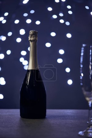 Photo for Selective focus of champagne bottle and glass with christmas lights bokeh - Royalty Free Image