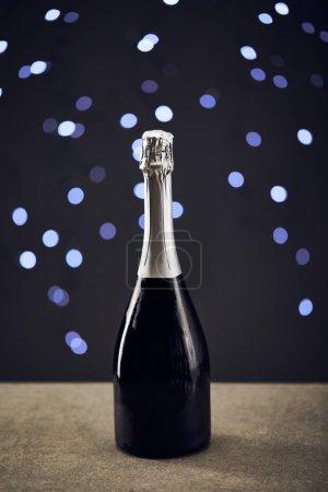 Photo pour Une bouteille de vin mousseux aux lumières de Noël floues - image libre de droit